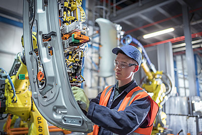 Apprentice engineer adjusting robot in car factory - p429m2138431 by Monty Rakusen