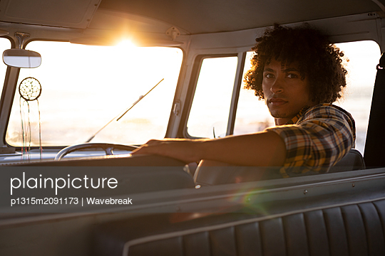Mixed-race man turning back to looking the camera in a camper van  - p1315m2091173 by Wavebreak