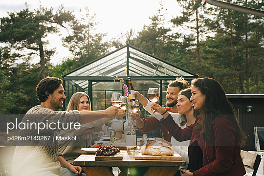 Male and female friends toasting wineglasses while enjoying dinner at garden party - p426m2149267 by Maskot