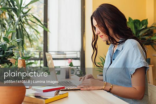 Caucasian woman using laptop at desk - p555m1410518 by Lumina Images