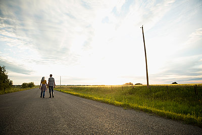 Couple farmers walking on road along idyllic farm at sunset - p1192m1493191 by Hero Images