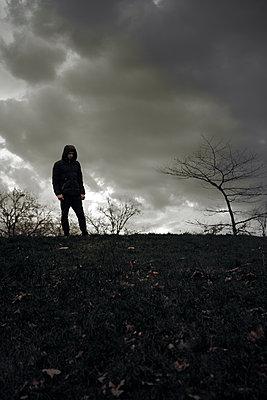 Silhouette eines Mannes mit Kapuze vor dunklen Wolken - p1248m1526420 von miguel sobreira