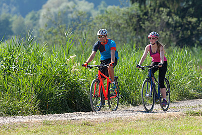 Man and teenage girl on a bicycle tour with trekking bikes - p300m1140763 by Daniel Simon