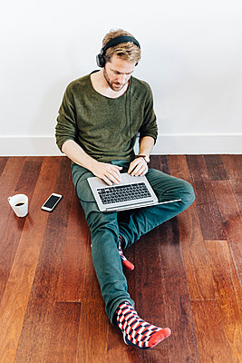 Man with headphones sitting on the floor at home using laptop - p300m1499638 by Giorgio Fochesato