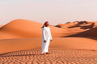 Bedouin in National dress standing in the desert, Wahiba Sands, Oman - p300m2104239 by Valentin Weinhäupl