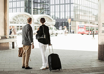 Rear view of business people with luggage standing outside railway station - p426m844665f by Maskot
