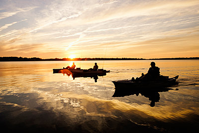 Silhouette of people fly fishing in kayaks on river - p555m1304972 by Roberto Westbrook