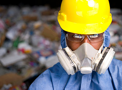 Portrait of male worker in hard hat and gas mask, in front of rubbish at recycling plant - p924m1197269 by InStock