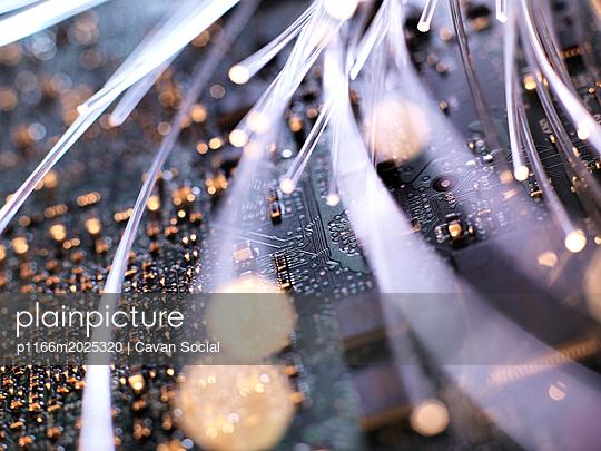 Close-up of illuminated fiber optics on circuit board of laptop computer - p1166m2025320 by Cavan Social