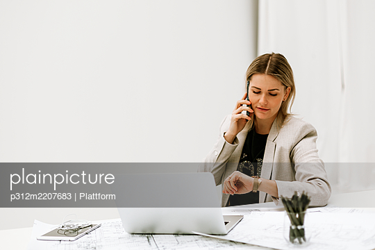 Businesswoman at desk talking via cell phone - p312m2207683 by Plattform