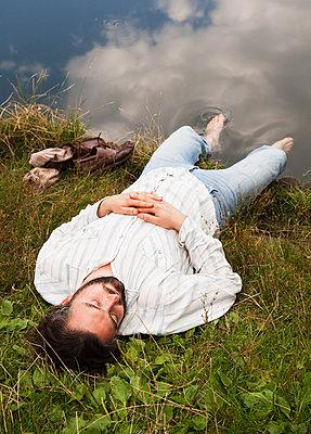 Mann ruht sich am Seeufer aus - p1008m1170001 von Valerie Schmidt