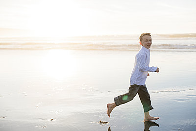 Smiling boy running while looking at front at the beach - p1166m2073869 by Cavan Images