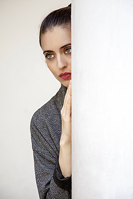 Woman peering from behind pillar, portrait - p1248m2193188 by miguel sobreira