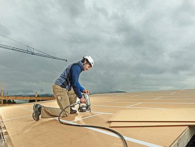 Austria, construction worker fixing medium-density fibreboard - p300m1567839 by Christian Vorhofer