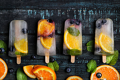 Homemade detox popsicles with blueberries, orange slices and mint leaves on black wood - p300m1581205 von Retales Botijero