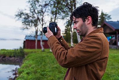 Sweden, Kiruna, Young man taking pictures of lake - p300m2042404 by Kike Arnaiz