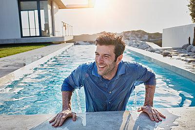 Südafrika, Western Cape, Yzerfontein, Immobilie, modernes Haus, Mann mit Anziehsachen im Pool, Sommer, Sonne, Lichtreflexionen, Lebensfreunde, Emotionen - p300m2286822 von Roger Richter