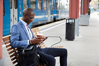 Businessman using smart phone while sitting with coffee at railroad station - p426m2072417 by Maskot