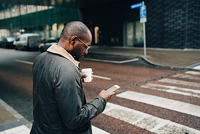 Side view of businessman with coffee using mobile phone while crossing road in city - p426m2074692 by Maskot