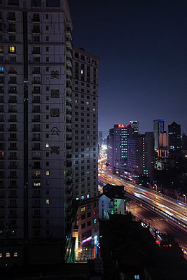 Night highway between buildings - p664m788112 by Yom Lam