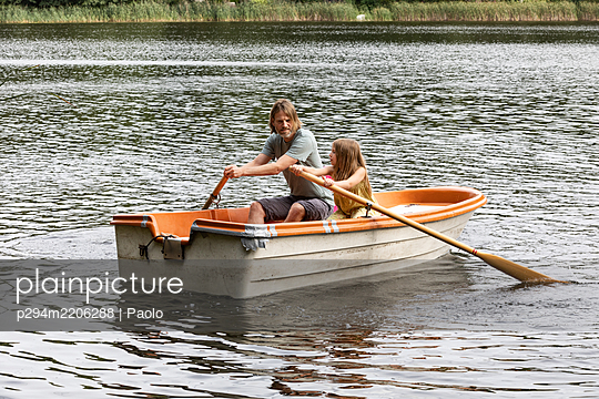 Father and daughter rowing together - p294m2206288 by Paolo