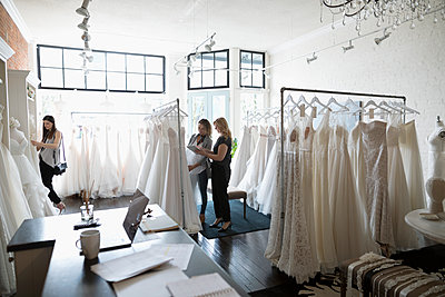 Bridal shop owner helping bride shopping for wedding dress - p1192m1583296 by Hero Images