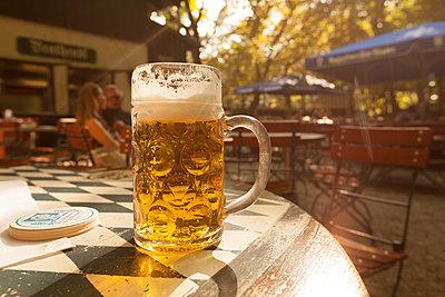 Beer mug on table in beer garden at evening twilight - p300m1506328 by Christina Falkenberg