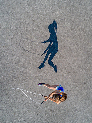 Aerial view of young woman skipping rope, shadow - p300m2005374 von Stefan Schurr
