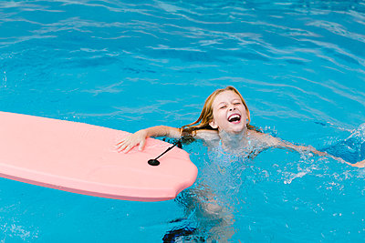 Cheerful girl playing in swimming pool - p300m2281378 by Lightsy Studio
