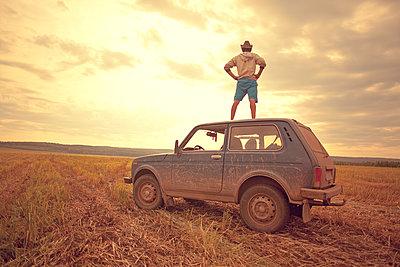 Mari man standing on car roof in rural field - p555m1420520 by Aliyev Alexei Sergeevich