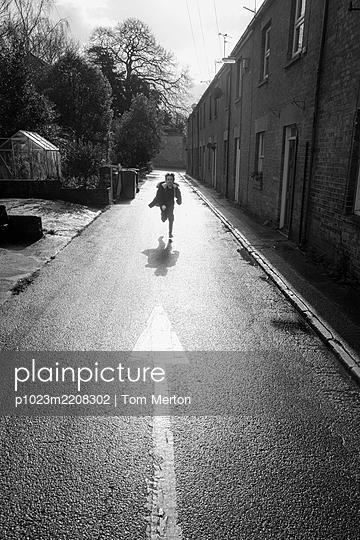 Boy running on sunny road - p1023m2208302 by Tom Merton