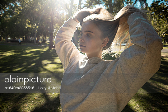 Teenage girl with blond hair in a park - p1640m2258516 by Holly & John