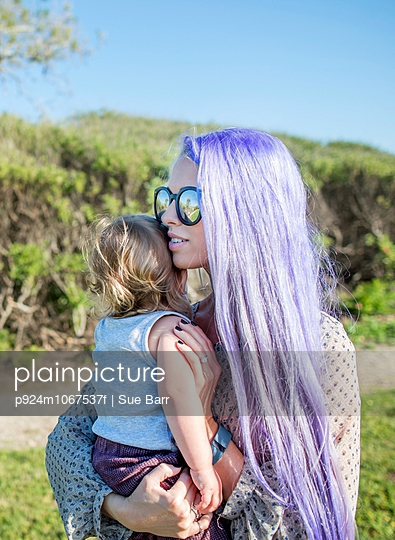 Young woman with long purple hair, holding baby daughter