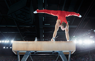 Male gymnast performing upside-down handstand on pommel horse in arena - p1023m1217748 by Chris Ryan
