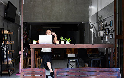 Woman sitting at wooden table using laptop and cell phone - p300m1535813 by Ivan Gener Garcia