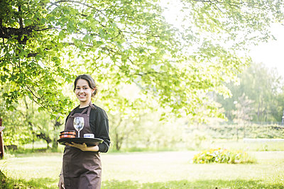 Portrait of confident young female waitress smiling while holding serving tray against plants - p426m2127594 by Maskot