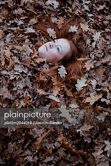 Rothaarige Frau liegt im Laub - p045m2044014 von Jasmin Sander