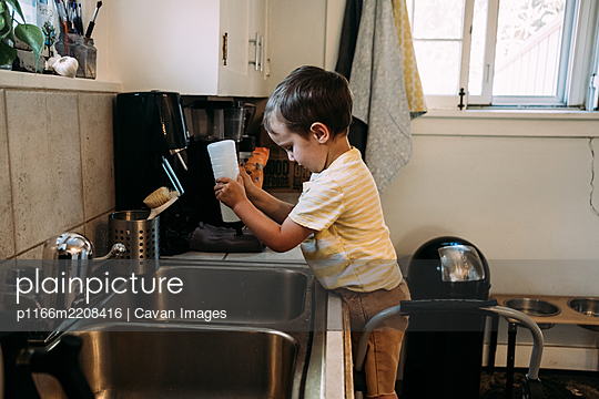 Little boy playing with squirt bottle at kitchen sink - p1166m2208416 by Cavan Images