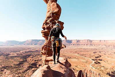 Rear view of female hiker walking on rock formation against clear sky during sunny day - p1166m1555586 by Cavan Images