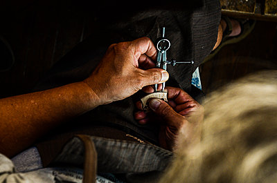Violin maker luthier changing bridge of a handmade baroque violin - p1166m2201777 by Cavan Images