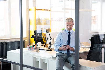 Mature businessman sitting office , using smartphone, reading messages - p300m1537626 by Florian Küttler