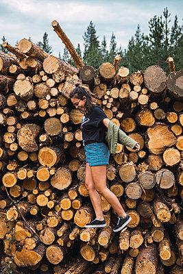 Happy young woman balancing on stack of wood - p300m2060835 by Kike Arnaiz