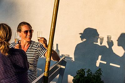 Happy women drinking champagne - p312m1229015 by Fredrik Schlyter