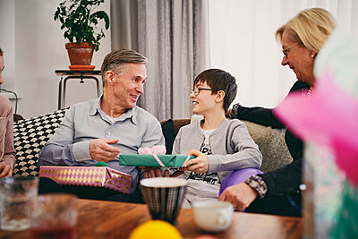 Happy grandfather receiving gifts from grandson at birthday party - p426m1580243 by Maskot