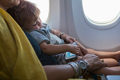Caucasian mother holding baby son on airplane - p555m1411386 by Marc Romanelli