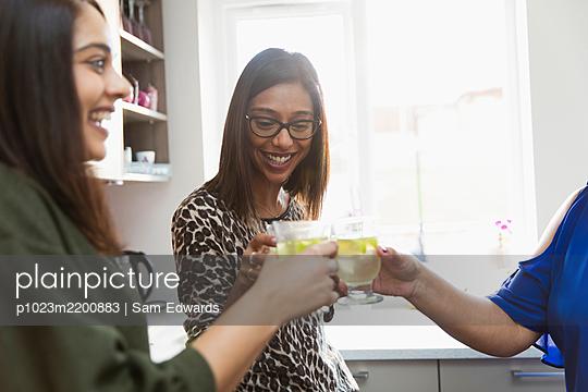 Happy women drinking in kitchen - p1023m2200883 by Sam Edwards