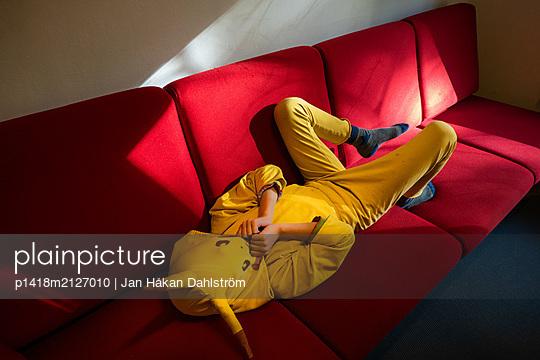 Little boy hiding in costume party dress - p1418m2127010 by Jan Håkan Dahlström