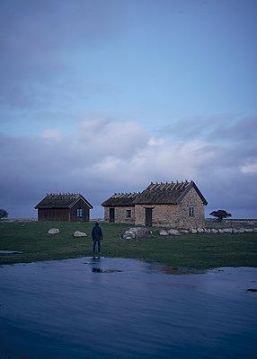 Mann steht vor Fischerhütten - p1124m1193516 von Willing-Holtz