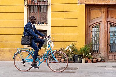 Young businessman riding bicycle in the city - p300m2198064 by Ezequiel Giménez