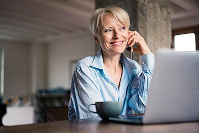 Smiling businesswoman with laptop and coffee cup looking away while talking on mobile phone at desk in home office - p300m2266988 by Robijn Page